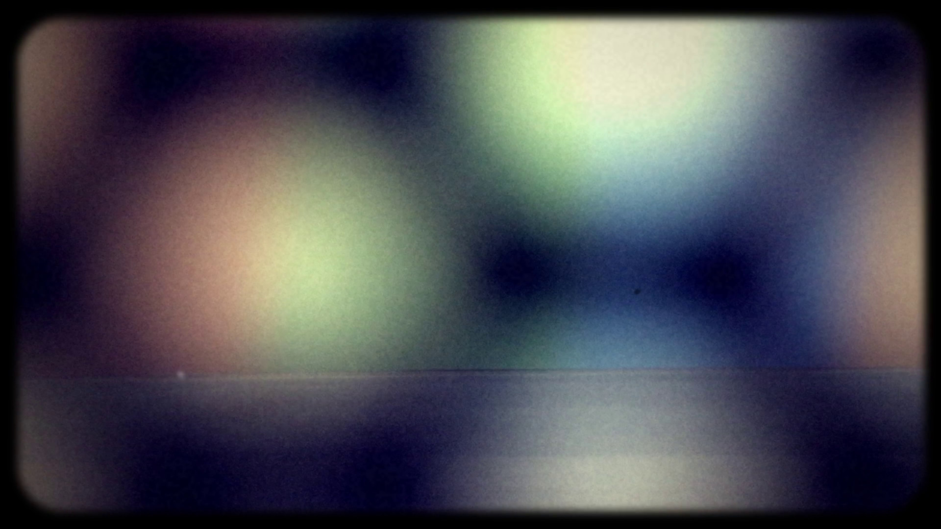 "Frame from the film ""Circulation"" showing blurred coloured circles."